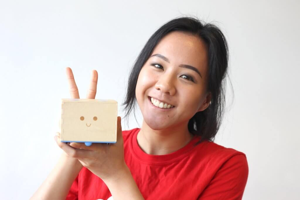 Sze-Von, Primo Toys employee, holding Cubetto, the wooden robot that teaches coding to children; coding for kids; teach kids to code