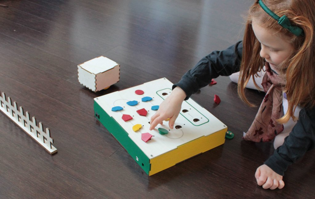 Girl playing with early version of Cubetto, the wooden toy teaching coding for kids