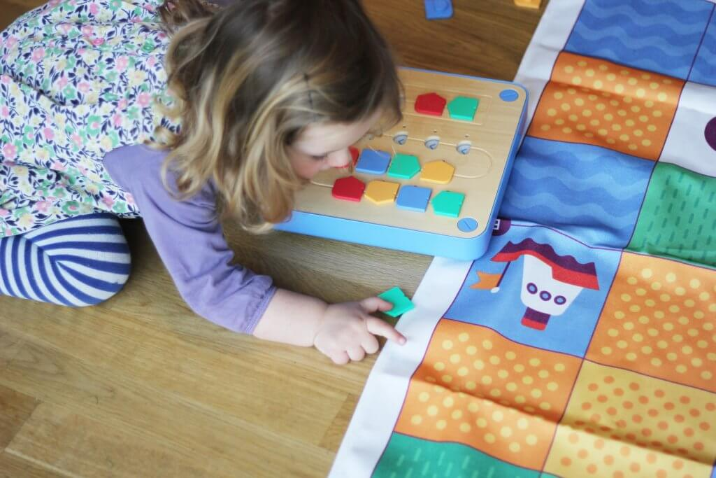 Child playing with Cubetto, the smart coding toy for kids