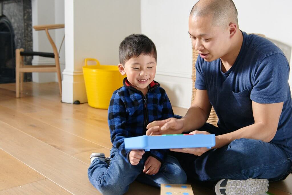 Child and father playing with Cubetto, the educational STEM toy for toddlers