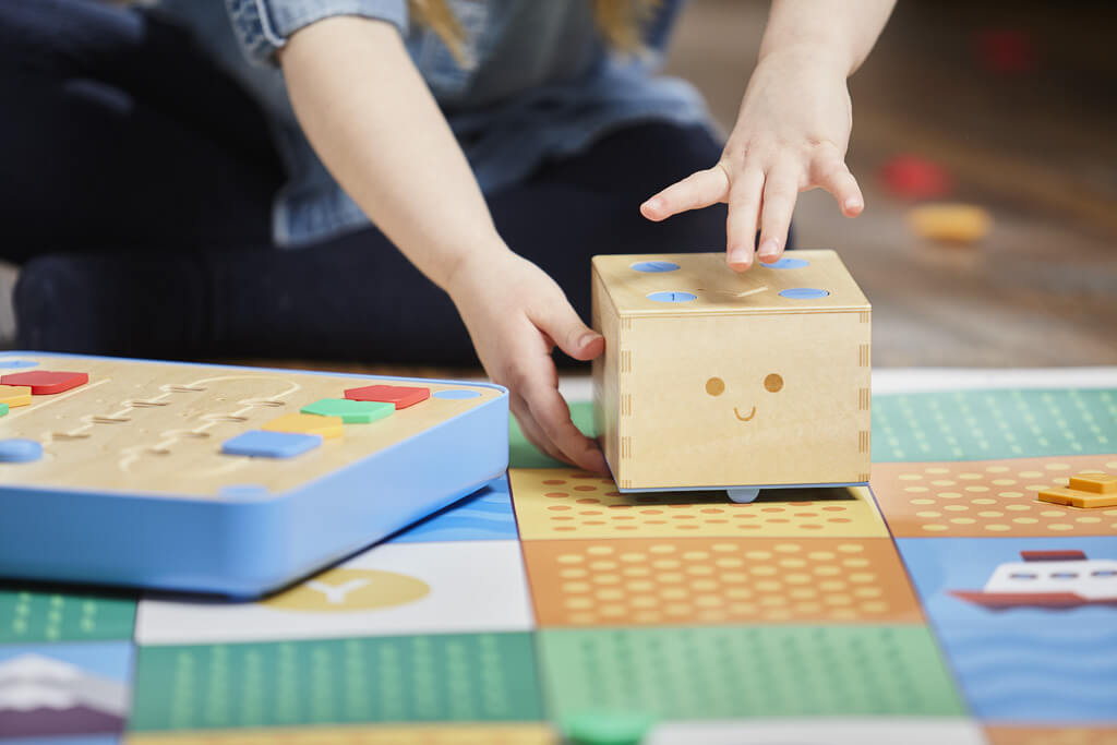 toddler on floor playing with educational toy cubetto with parent and space adventure map