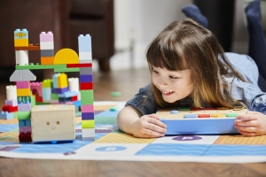 kid on floor playing the cubetto playset, holding interface board, lying on adventure world map