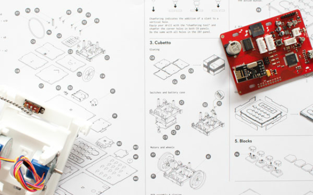photograph assembly guide, cubetto circuit board, and blueprint constructing cubetto