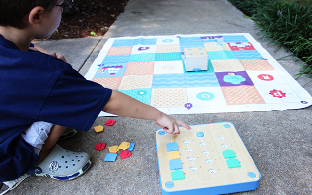 kids engaging with educational stem toy cubetto
