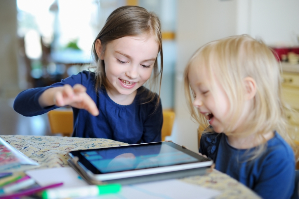 two sisters playing on a digital tablet. stem toys for toddlers, learning toys for toddlers