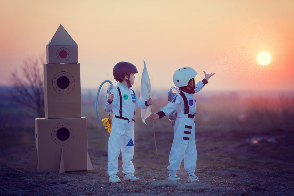 Two adorable children, boy brothers, playing in park on sunset, dressed like astronauts, imagining they are flying on the moon; educational science toys; science and educational toys; STEM toys for toddlers
