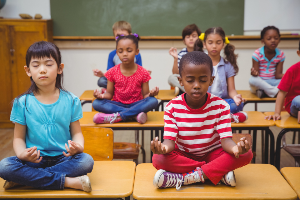 Pupils meditating in lotus position on desk