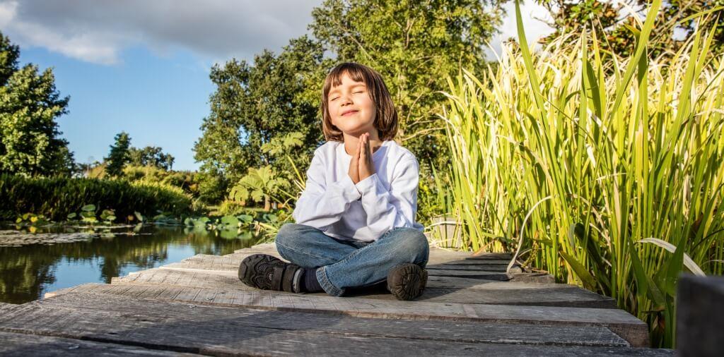 child meditating near pond