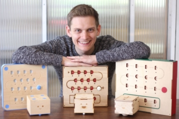 Ben Callicott, Head of Product at Primo Toys, with three iterations of Cubetto, the wooden robot who teaches computer programming to kids