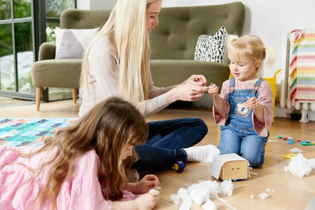 Family with mother and two daughters playing with Cubetto, the wooden robot who teaches kids to code. Educational toys, STEM toys for toddlers