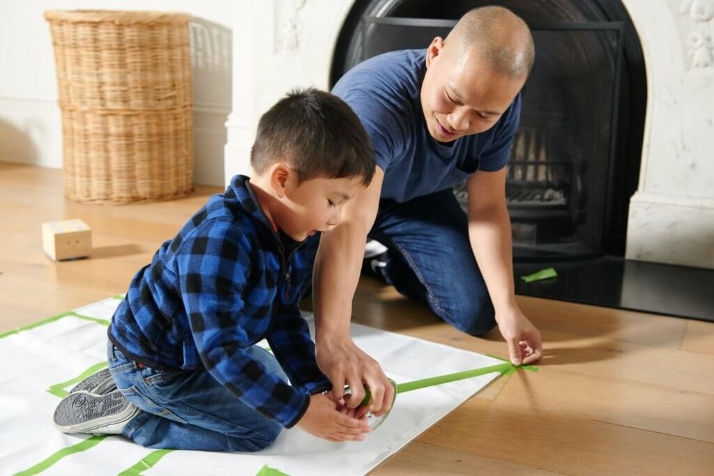Child with father making a masking tape map for Cubetto, the wooden robot who teaches kids coding. Programming for kids.