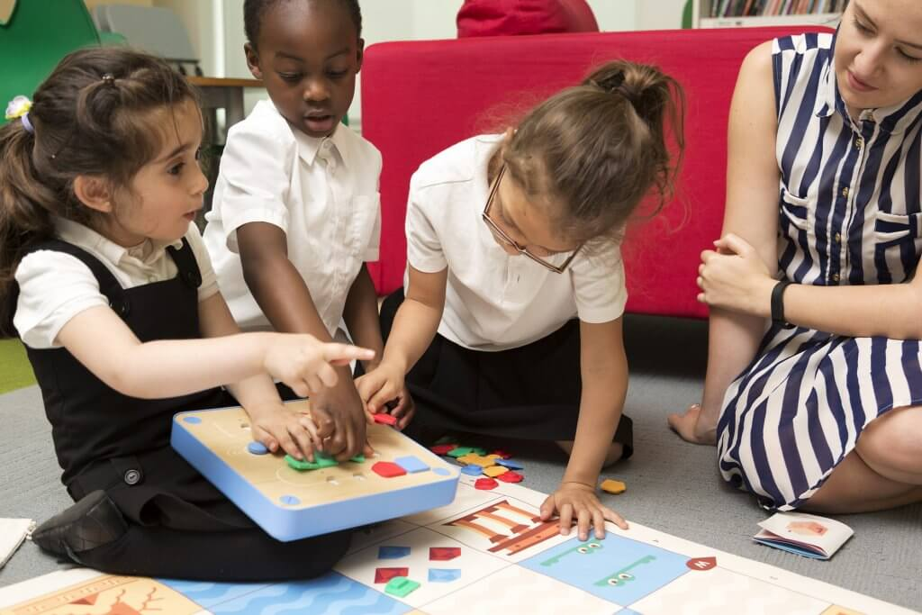 Teacher and children learn programming for kids with Cubetto